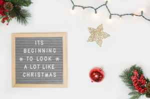 it s beginning to look a lot like christmas board decor beside star and red bauble flatlay photography